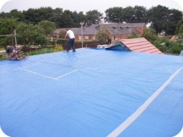 Tarpaulin is laid and taped at the joints to ensure water does not get into the existing building.