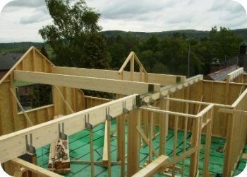 The first floor timber frame structure is constructed directly on top of the first floor structure and the roof beams begin to for the roof structure.