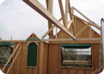 Once the timber frame panels are erected, the new roof structure is crained into place.